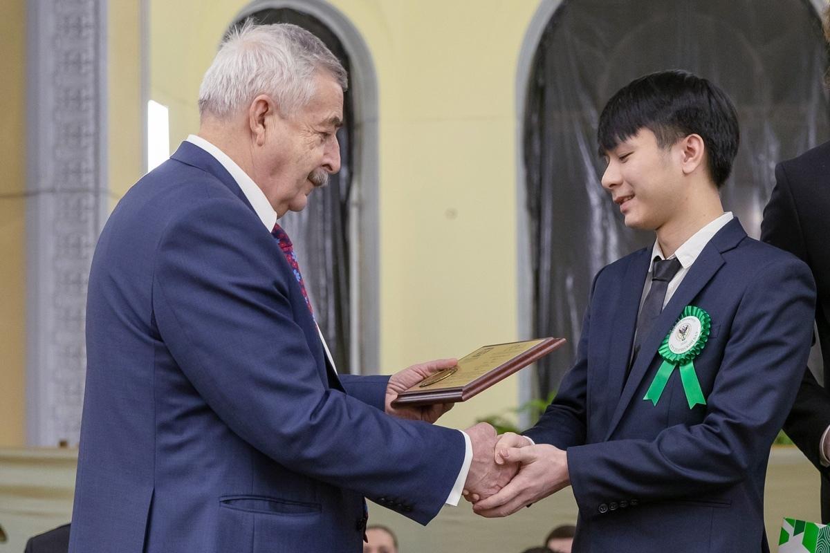 Руководитель административного аппарата ректора СПбПУ Владимир Глухов вручает Нгуен Тиен Хоангу памятную плакетку с медалью