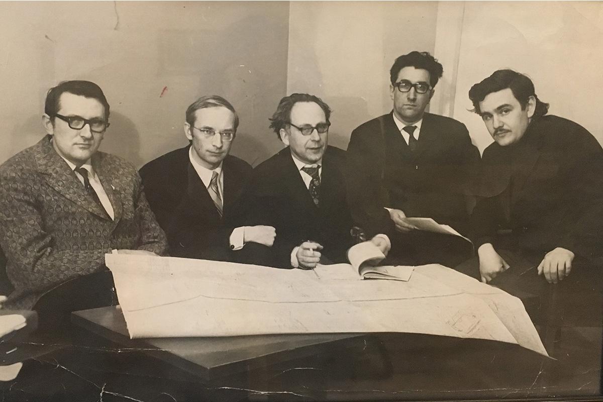 На фото 1974 г.: справа Л.А. Вайсберг, следующий – профессор Илья Израилевич Блехман. Фото с чертежом принципиально новой машины. Этот коллектив был удостоен правительственной премии